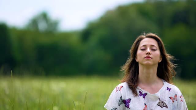 Hingebungsvolle-junge-Frau-mit-geschlossenen-Augen-sitzt-und-meditiert-im-Freien-Gefühl-wind