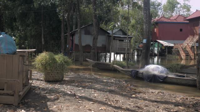 Hochwasser-in-Pfahlbauten-mit-kleinen-Einbaum-im-Innenhof-
