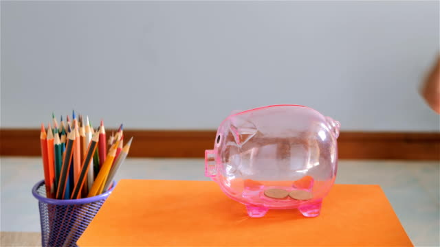 Hand-of-boy-putting-coin-into-piggy-bank-Saving-for-education-fund-concept