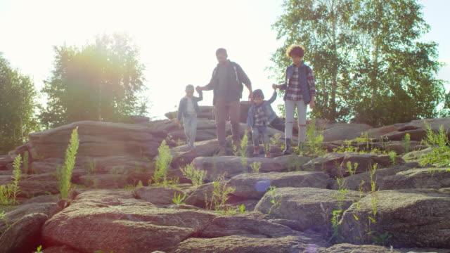 Aktive-Familie-mit-Kindern-zu-Fuß-durch-Felsen