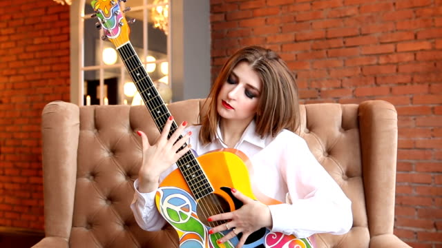 Girl-in-white-shirt-posing-with-a-guitar-in-hippie-style