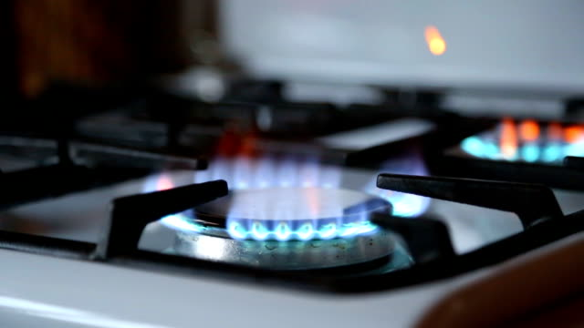 Stove-top-burner-igniting-into-a-blue-cooking-flame