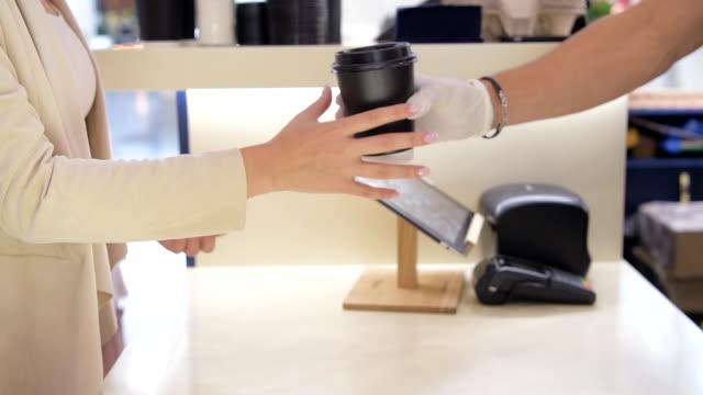 Mujer-toma-taza-de-papel-de-pago-mostrador-de-café-para-llevar-Cerrar-tiro-de-manos