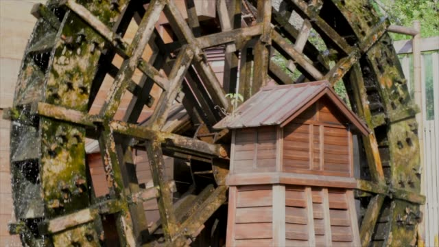 scenic-side-view-of-an-old-river-water-wheel-spinning-in-the-sun