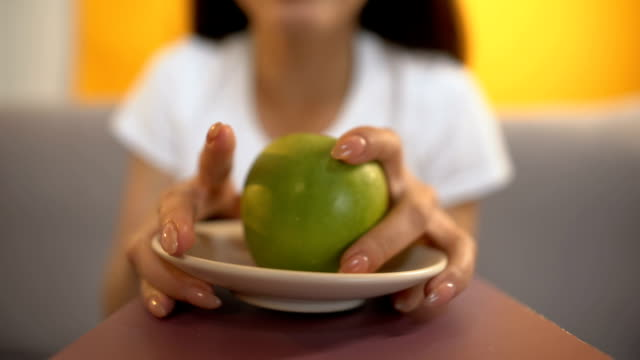 Person-serves-apple-to-starving-girl-strict-veganism-and-lack-of-vitamins-diet