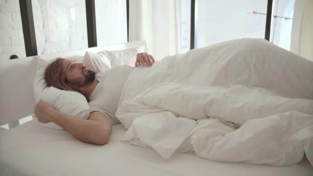 Sleeping-Man-Waking-Up-In-Morning-From-Noise-Outside