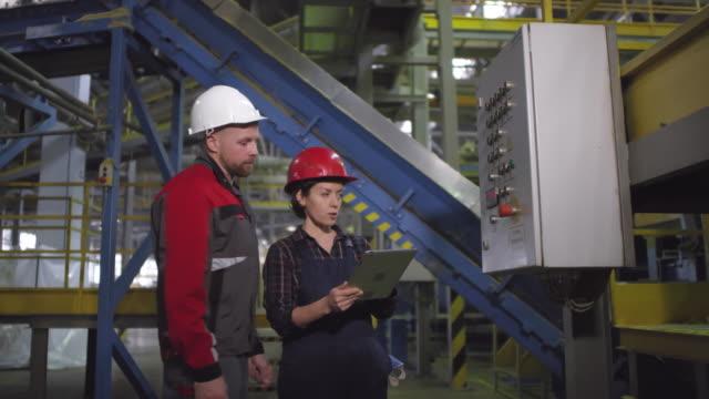 Männlicher-Ingenieur-berät-Kollegin-in-der-Fabrik