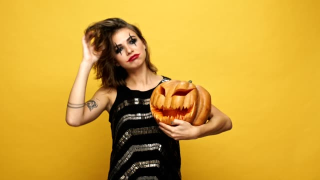 Young-pretty-funny-lady-with-scary-make-up-hugging-with-pumpkin-isolated-over-yellow