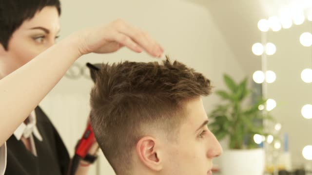 Hairdresser-drying-and-styling-male-hair-after-cutting-in-hairdressing-salon-Close-up-barber-styling-hair-with-dryer-after-washing-Finish-hairdressing-in-beauty-studio