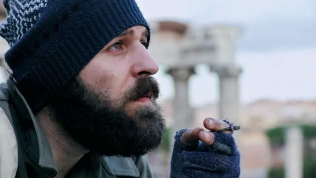Thoughtful-and-pensive-homeless-smoking-a-cigarette