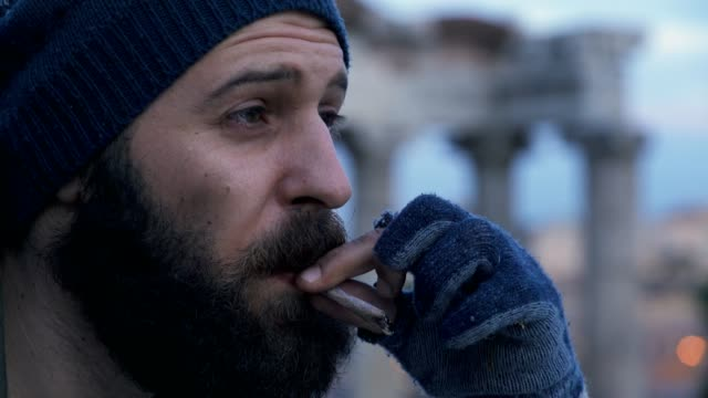 Thoughtful-dirty-homeless-lighting-cigarette--outdoor