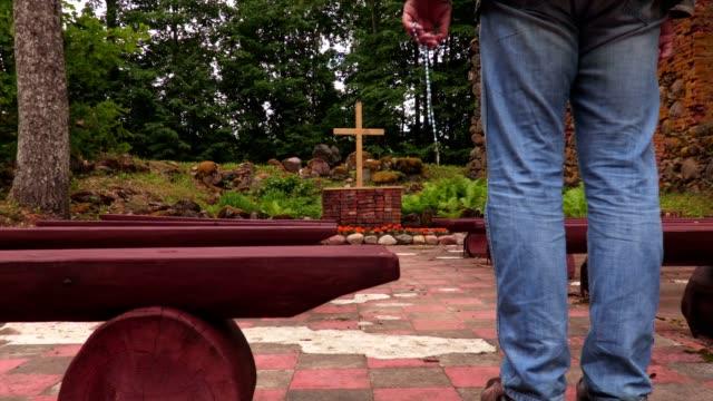 Mann-mit-Rosenkranz-zu-beten-gehen-in-der-Nähe-von-Kreuz