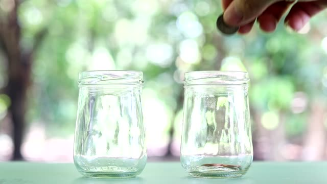 Savings-money-in-the-jar-Hand-put-coins-falling-into-the-jar-