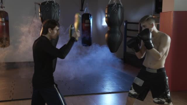 Un-boxeador-profesional-con-su-entrenador-en-el-ring-entrena-la-velocidad-de-reacciones-y-huelgas-El-hombre-en-el-gimnasio-es-la-formación-en-el-contexto-de-las-peras-de-boxeo-por-encima-del-suelo-una-neblina-gris-opaco