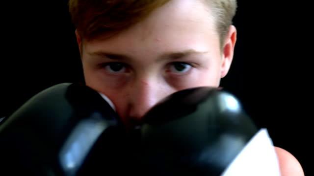 Der-junge-Boxer-steht-auf-einem-dunklen-Hintergrund,-der-Junge-hat-ein-graues-T-shirt,-sein-Gesicht-ist-fast-mit-behandschuhten-Händen-bedeckt.-Der-Junge-hat-helle-kurze-Haare-und-dunkle-Augen