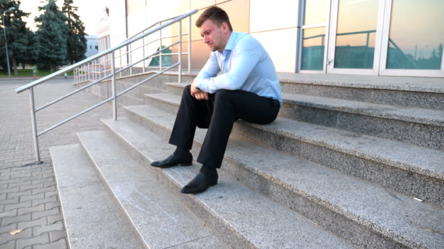 Close-up-of-upset-sad-manager-sitting-on-stairs-near-office-building-and-crying-Desperate-young-businessman-got-a-very-bad-news-on-phone-and-feeling-despair-outdoor-Concept-of-financial-crisis