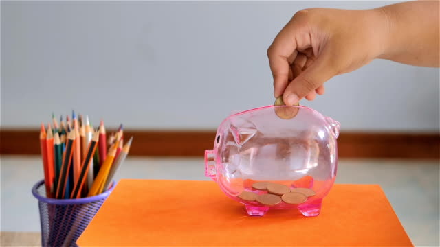 Slow-Motion-Hand-of-boy-putting-coin-into-piggy-bank-Saving-for-education-fund-concept