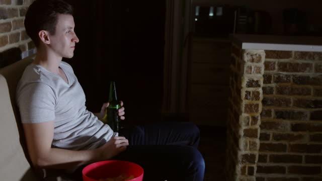 Junger-Mann-vor-dem-Fernseher-mit-Bier-und-chips