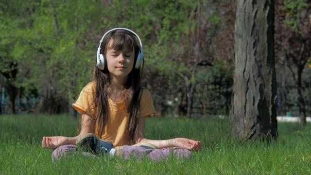 Mädchen-mit-Kopfhörern-in-Lotus-Pose.