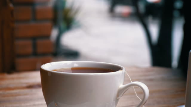 White-Cup-of-Hot-Tea-on-the-Table-in-a-Cafe-on-the-Background-of-the-Street-Window