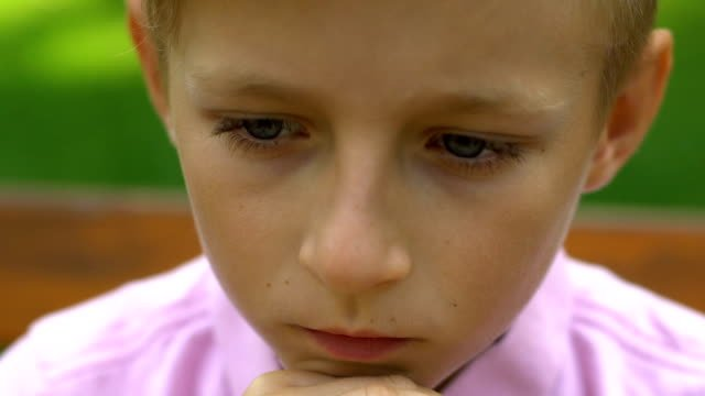 Unhappy-little-boy-with-cane-sitting-on-bench-in-park-handicapped-sad-child