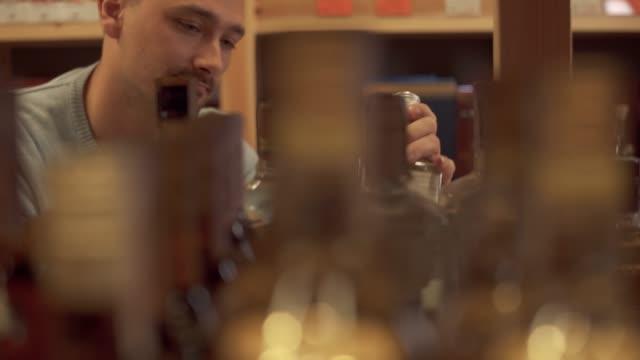 Porträt-von-fröhlicher-Mensch-ist-Gin-Flasche-aus-dem-Regal-nehmen-Kunde-ist-Getränk-mit-dem-Spirituosengeschäft-entschieden-