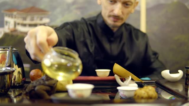 Master-man-pours-green-tea-from-a-glass-teapot-into-a-white-mug
