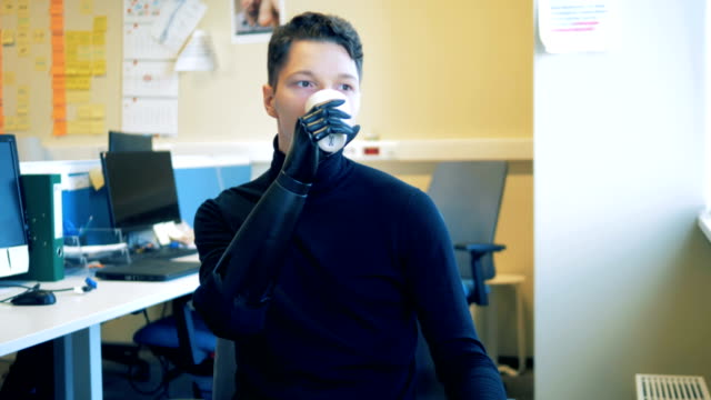 Young-man-with-an-artificial-bionic-futuristic-hand-is-drinking-from-a-cup-Man-of-future-concept-
