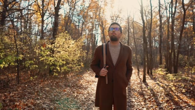 Gut-aussehender-Mann-mit-Brille-ein-Spaziergang-im-Herbstwald-tagsüber-umzusehen
