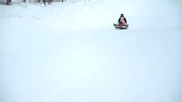 Mother-and-Daughter-Riding-on-a-Sledding-Tubing