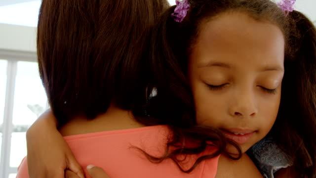 Vista-frontal-de-la-linda-niña-negro-abrazando-a-su-madre-en-el-salón-de-casa-confortable-4k