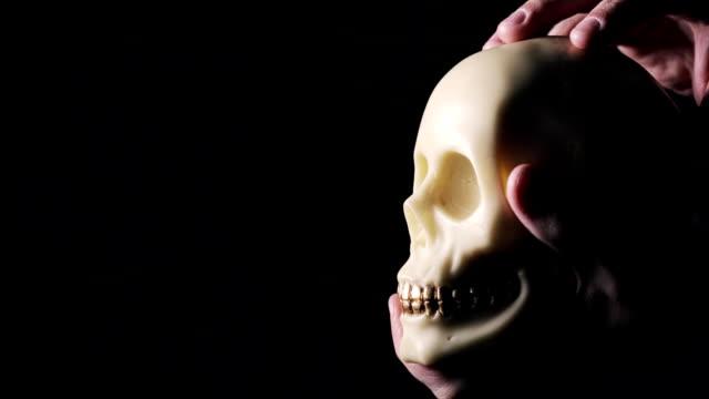 Mano-del-hombre-manteniendo-y-acariciando-el-cráneo-con-dientes-de-oro-sobre-fondo-negro