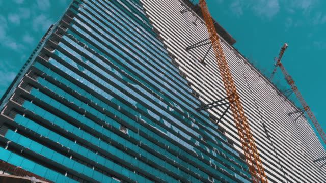 Kran-auf-einer-Baustelle-gegen-den-blauen-Himmel-baut-einen-neuen-Wolkenkratzer-Gebäudebau
