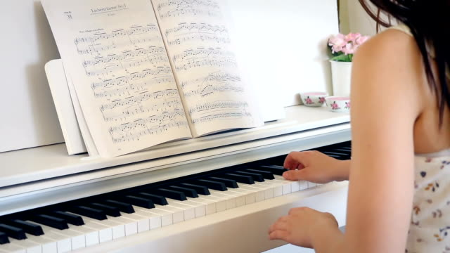 Young-brunette-woman-is-playing-the-piano-in-bright-room-from-back-hand-held