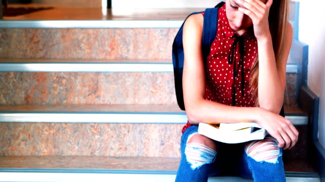 Sad-schoolgirl-sitting-alone-on-staircase