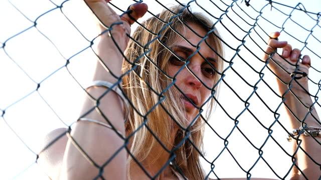 frustrado-y-triste-mujer-encarcelada-detrás-de-una-red---cámara-lenta
