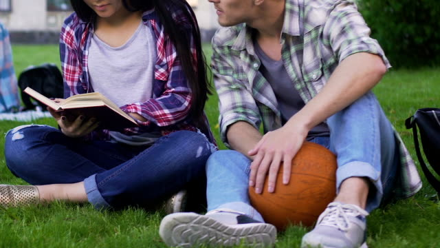 Students-sitting-on-lawn-together-girl-reading-and-guy-talking-to-her-flirt