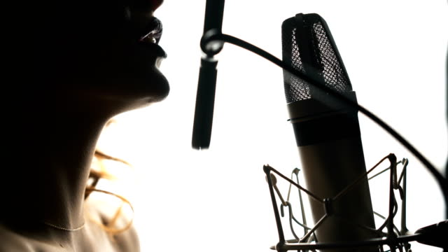 Beautiful-woman-singing-into-a-microphone-in-a-recording-studio-