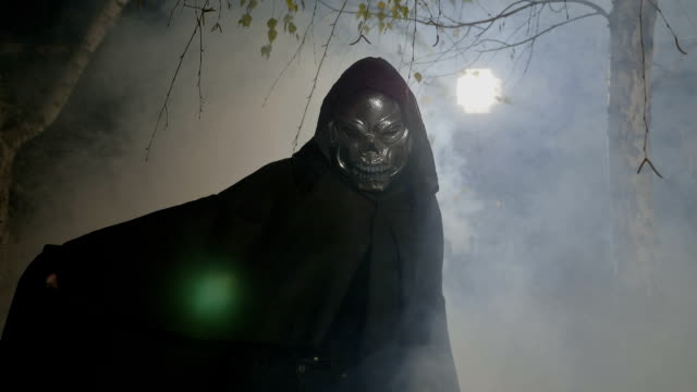 Halloween-movie-scene-with-an-adult-wearing-a-skelton-mask-and-mantle-frightening-the-camera-in-a-foggy-forest