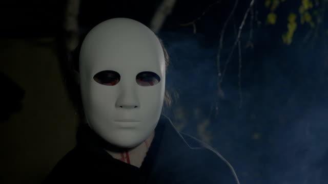 Nahaufnahme-von-einem-Halloween-Zombie-mit-einer-weißen-Maske-auf-dem-Gesicht-direkt-auf-Kamera