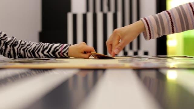 Ein-Elternteil-und-Kind-spielen-ein-Brettspiel-auf-schönen-modernen-Tisch-und-Raum