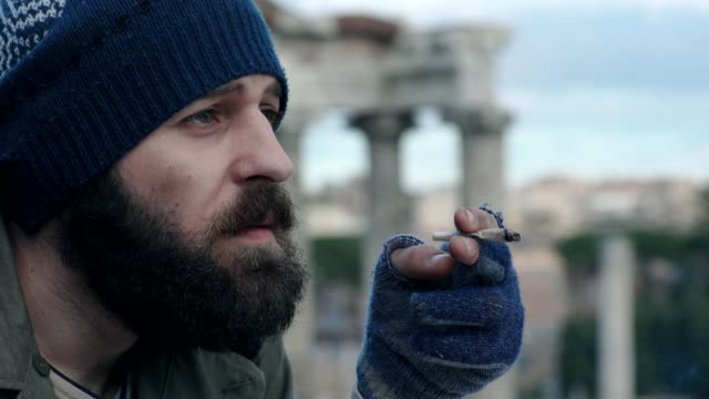 Sad-pensive-homeless-smoking-cigarette--close-up-portrait