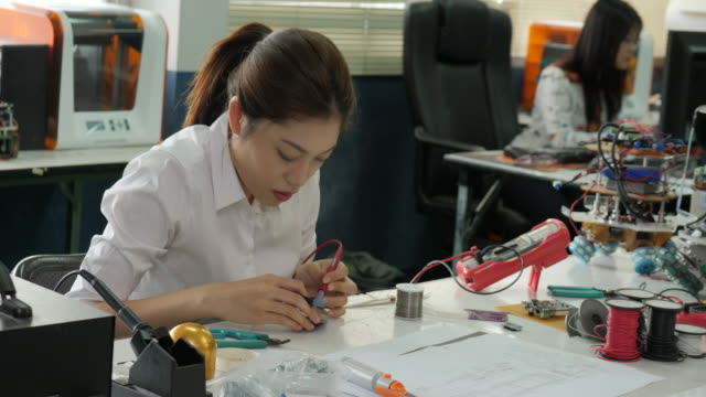 Woman-electronics-engineer-is-measuring-the-signal-in-the-electrical-circuit-in-her-workshop-Girl-student-are-studying-electronics-in-classroom-