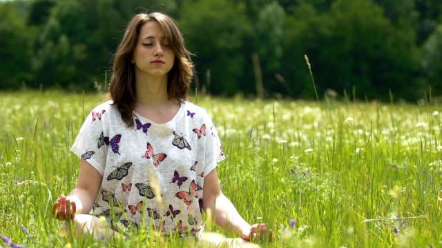 Meditación-al-aire-libre-en-campo-verde-flor-mujer-joven-se-sienta-en-posición-de-loto