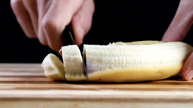 Hombre-es-cortar-plátano-en-tabla-de-cortar-en-cámara-lenta
