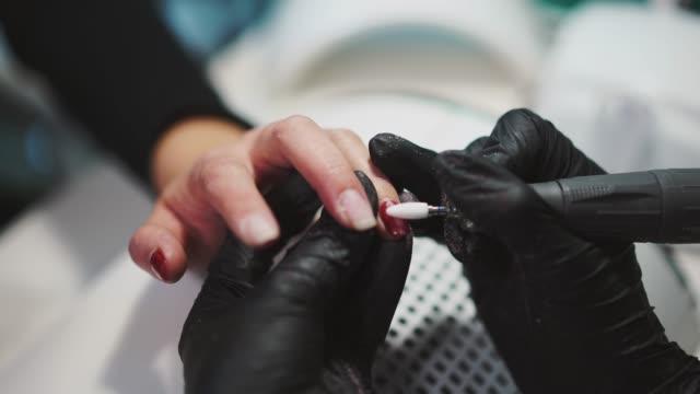 manicurista-es-eliminación-de-pulimento-del-gel-rojo-de-los-dedos-del-cliente-con-el-uso-de-equipos-profesionales-