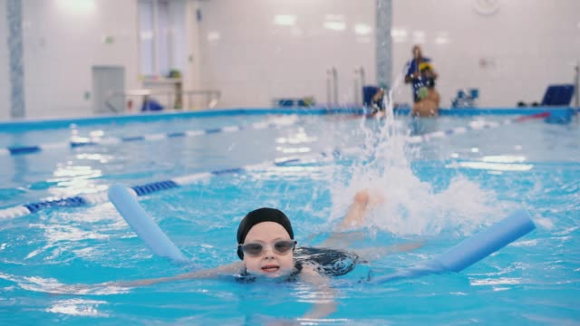 Schwimmkurse-für-Kinder-in-den-Pool---schönes-hellhäutige-Mädchen-im-Wasser-schwimmt
