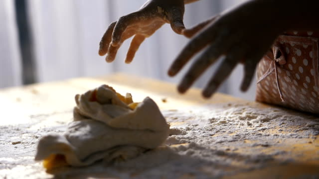 Kids-hands-preparing-dough-for-pizza-or-bread-on-table-slow-motion-