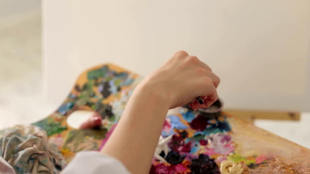 The-artist-mixes-oil-paints-on-a-palette-with-a-brush-close-up-
