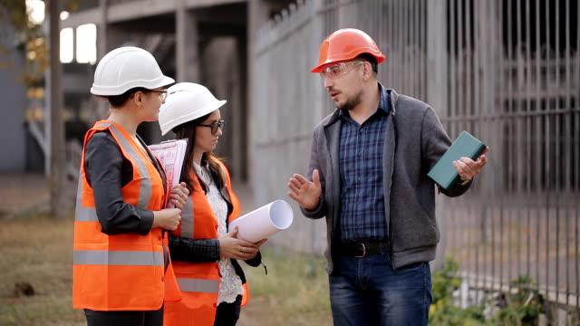 El-ingeniero-se-comunica-con-las-mujer-representantes-en-la-obra-verificar-los-dibujos-con-el-avance-real-de-obra